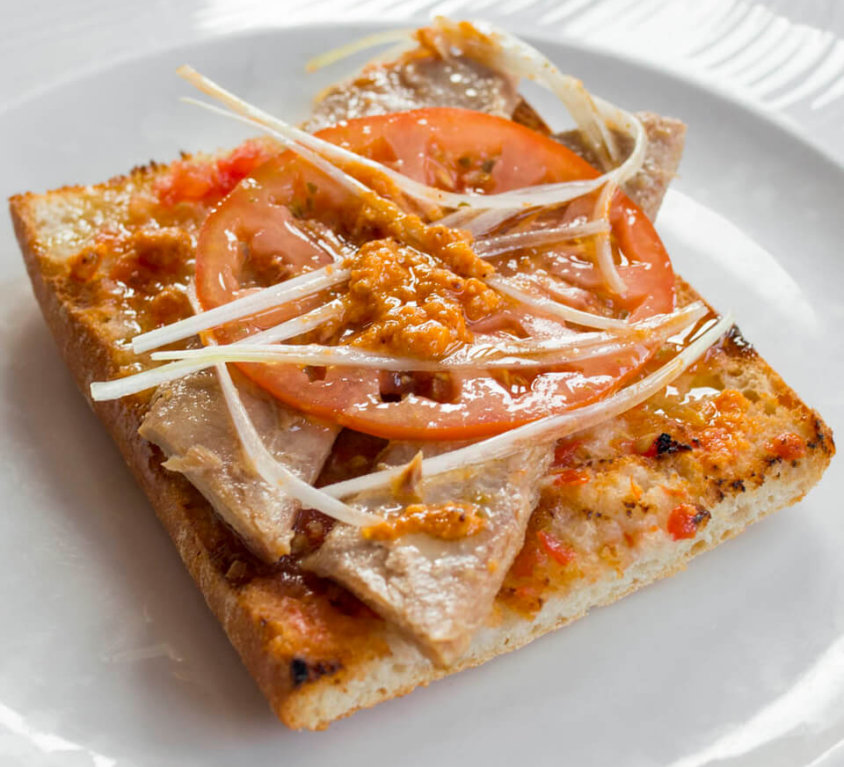 Coca bread with tuna belly, raf tomato, onion and romesco